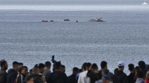 People look at a rescue boats arriving at the scene of a helicopter crash in the Mediterranean sea off the coast of the commune of Bouharoun in Tipasa province, about 30 kilometres west of Algiers in northern Algeria on December 16, 2020. (Photo by Ryad KRAMDI / AFP)