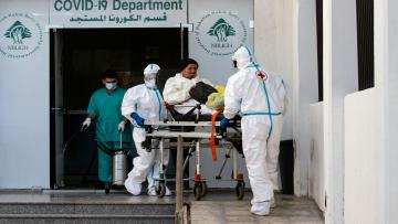 Members of the Lebanese Red Cross wearing hazmat suits, transfer an elderly coronavirus patient to the COVID-19 department of the Nabih Berri university hospital, in the southern Lebanese city of Nabatiyeh, on January 9, 2021. - Since the start of the Covid-19 pandemic, Lebanon has recorded nearly 200,000 cases including 1,537 deaths, according to health ministry figures. Health professionals have warned that the latest surge in cases risked causing catastrophe across Lebanon, which is already suffering from the aftermath of a devastating August explosion in Beirut and a dire economic crisis. (Photo by Mahmoud ZAYYAT / AFP) (Photo by MAHMOUD ZAYYAT/AFP via Getty Images)