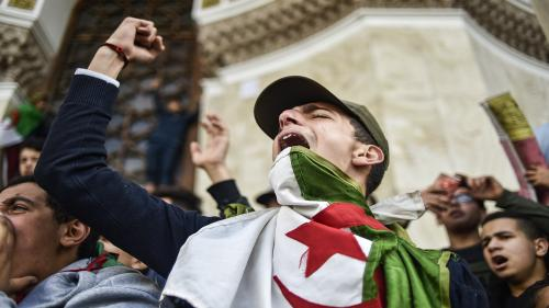 TOPSHOT - Algerian students shout slogans as they demonstrate with national flags outside the Main Post Office in the centre of the capital Algiers on March 10, 2019 against ailing Algerian President Abdelaziz Bouteflika's bid for a fifth term. (Photo by RYAD KRAMDI / AFP)RYAD KRAMDI/AFP/Getty Images