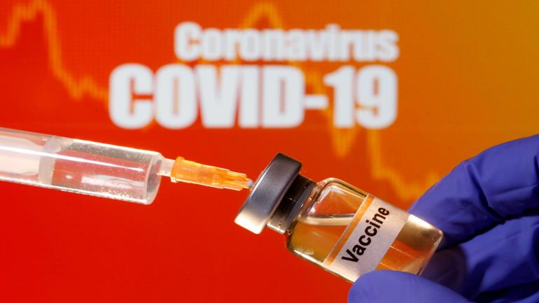 """FILE PHOTO: A small bottle labeled with a """"Vaccine"""" sticker is held near a medical syringe in front of displayed """"Coronavirus COVID-19"""" words in this illustration taken April 10, 2020. REUTERS/Dado Ruvic/Illustration -/File Photo"""