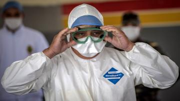 A member of the medical staff at Moroccos's military field hospital in Nouaceur, South of Casablanca, adjusts his goggles on April 18, 2020 as staff prepared to receive patients of the coronavirus pandemic. - Military hospitals have been reordered to maximise bed capacity, he said, adding that two field hospitals had been deployed to the coastal Casablanca region. Morocco had recorded 2,670 confirmed cases of coronavirus and 137 deaths, while over 280 have officially recovered. The North African kingdom has closed its borders and imposed a lockdown, enforced by security forces, to stem the spread of the disease. (Photo by FADEL SENNA / AFP) (Photo by FADEL SENNA/AFP via Getty Images)