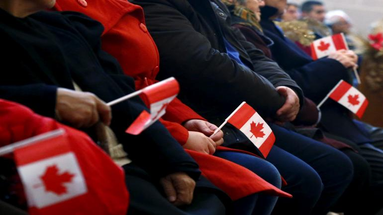 FILE PHOTO: Syrian refugees hold Canadian flags as they take part in a welcome service at the St. Mary Armenian Apostolic Church at the Armenian Community Centre of Toronto in Toronto, Ontario, Canada, December 11, 2015. REUTERS/Mark Blinch/File Photo