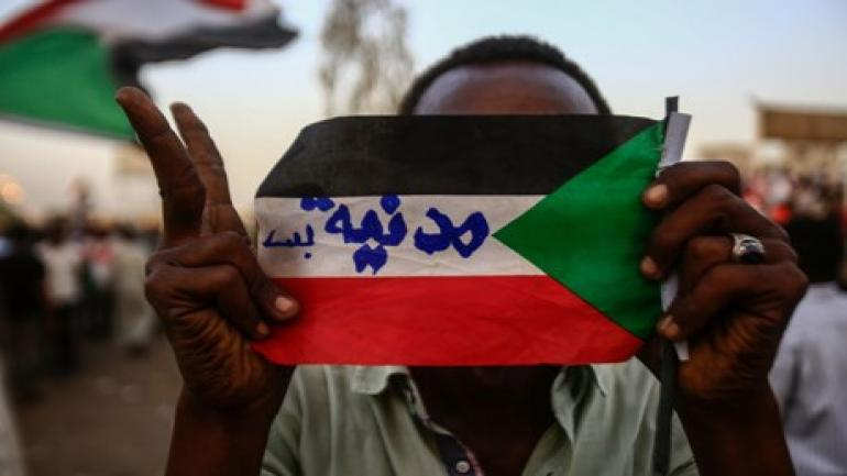 """A Sudanese protester holds the national flag with writings reading in Arabic """"Civilian Only"""" during a rally outside the army headquarters in Khartoum on May 2, 2019. - Sudan's prosecutor general ordered the questioning of deposed president Omar al-Bashir over money-laundering and """"financing terrorism"""", as protesters staged a vast rally in Khartoum to demand a civilian government. (Photo by ASHRAF SHAZLY / AFP)"""