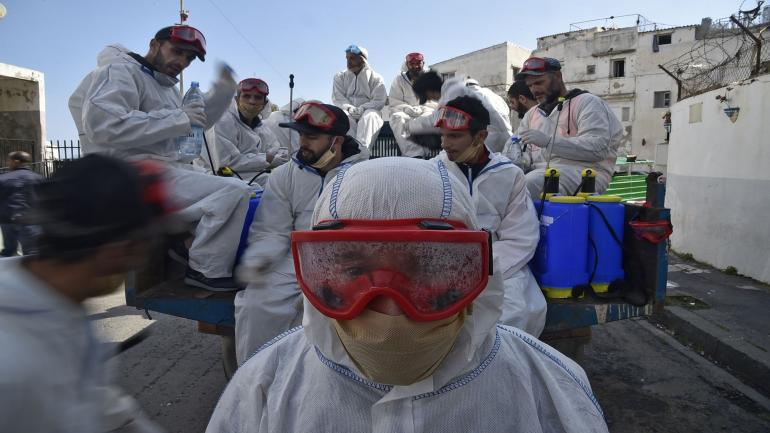 Municipal workers dressed in protective gear rest while on duty disinfecting a street during the COVID-19 coronavirus pandemic in the Bab el-Oued district of Algeria's capital Algiers on April 9, 2020. (Photo by RYAD KRAMDI / AFP) (Photo by RYAD KRAMDI/AFP via Getty Images)