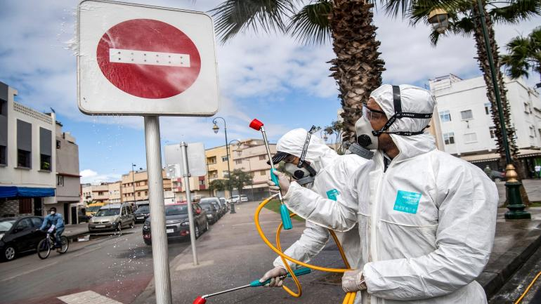 """A Moroccan health ministry worker disinfects a """"no entry"""" roadsign in the capital Rabat on March 22, 2020. - A public health state of emergency went into effect in the Muslim-majority country late on March 20, and security forces and the army have been deployed on the streets to combat the spread of COVID-19 coronavirus disease. People have been ordered to stay at home, and restrictions on public transport and travel between cities are also in place. (Photo by FADEL SENNA / AFP) (Photo by FADEL SENNA/AFP via Getty Images)"""