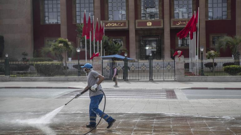 A worker disinfects a main avenue outside the parliament building in a bid to prevent the spread of coronavirus on Wednesday in Rabat, Morocco.The country imposed sudden, sweeping restrictions on travel.