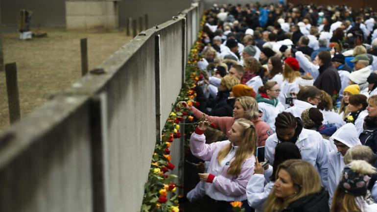 People stuck flowers in remains of the Berlin Wall during a commemoration ceremony to celebrate the 30th anniversary of the fall of the Berlin Wall at the Wall memorial site at Bernauer Strasse in Berlin, Saturday, Nov. 9, 2019. (AP Photo/Markus Schreiber)