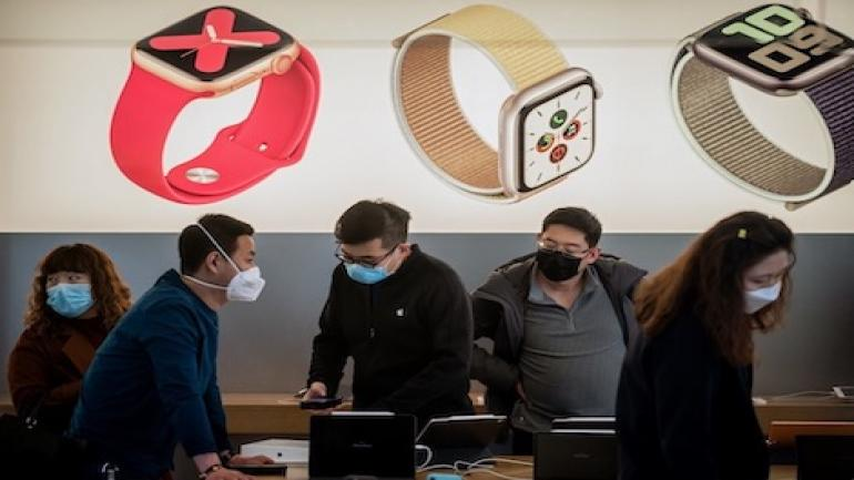 In this picture taken on March 11, 2020 an Apple staff (C) and customers wearing face masks as a preventive measure against the COVID-19 coronavirus are seen inside of an Apple shop in Beijing. - The number of fresh infections at the epicentre of China's COVID-19 coronavirus epidemic dropped to a new low on March 12 but the country imported more case from abroad. (Photo by NICOLAS ASFOURI / AFP)
