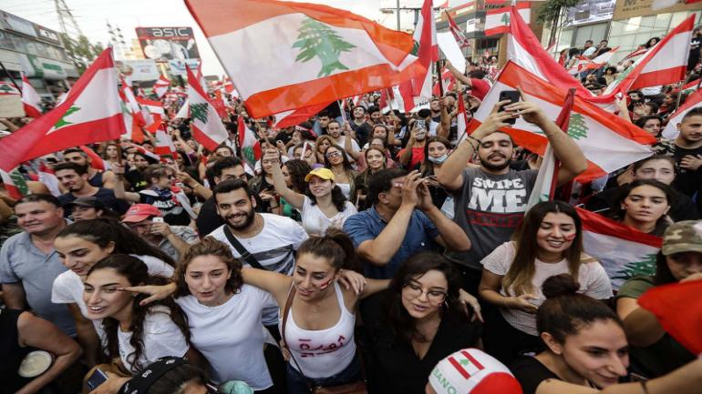 Lebanese demonstrators wave national flags on a highway linking Beirut to north Lebanon in Zouk Mosbeh on Oct. 19. JOSEPH EID/AFP via Getty Images