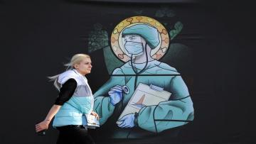 """A woman walks by a depiction of a medical staff wearing protective equipment, executed in the style of orthodox icons, in Bucharest, Romania, Wednesday, April 29, 2020. The artwork, among others depicting medical staff in the manner of religious icons, created by designer Wanda Hutira, is part of a campaign called Thank You Doctors, meant to raise awareness to the work of medical staff fighting the COVID-19 pandemic. Following public pressure by Romania's influential Orthodox church the artworks, described as """"blasphemous"""" will be removed from all locations in the Romanian capital, according to the agency behind the project. (AP Photo/Vadim Ghirda)"""