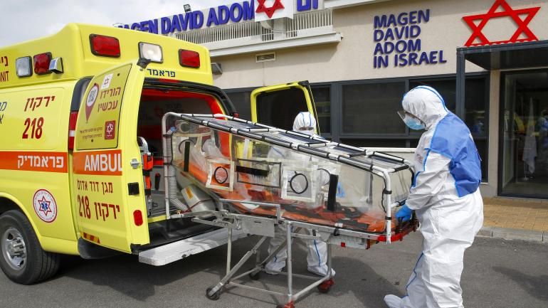 Israeli Paramedics of Maguen David Adom (Israel's National Emergency Pre-Hospital Medical Organisation) at the coronavirus national operations center unload a containment chamber during a coronavirus response training exercise in the central Israeli city of Kiryat Ono on February 26, 2020. - Some 80,000 people are infected worldwide, including nearly 2,800 outside China, and more than 2,700 have died worldwide, according to the latest toll from the World Health Organization. (Photo by JACK GUEZ / AFP)