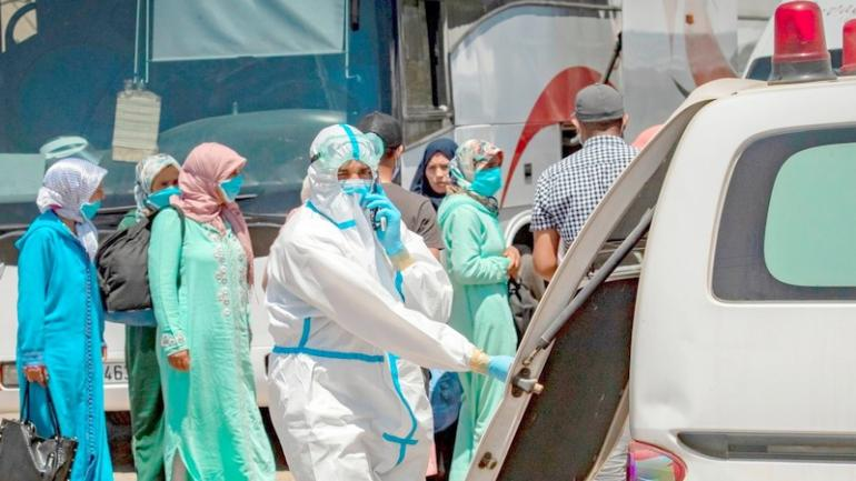 Moroccans, who tested positing for Covid-19, arrive in a parking lot in the town of Moulay Bousselham, north of the capital Rabat, on June 20, 2020, ahead of being transferred to a medical center in another city. - Morocco reported a record single-day rise in novel coronavirus cases on Friday after an outbreak was discovered in red fruit packing plants in a rural area northeast of Kenitra city, prompting Rabat to tighten restrictions in the region. The North African kingdom reported more than 500 cases on Friday, mainly in Kenitra, having recorded on average fewer than 100 new COVID-19 cases daily since confirming its first cases in early March. (Photo by FADEL SENNA / AFP) (Photo by FADEL SENNA/AFP via Getty Images)