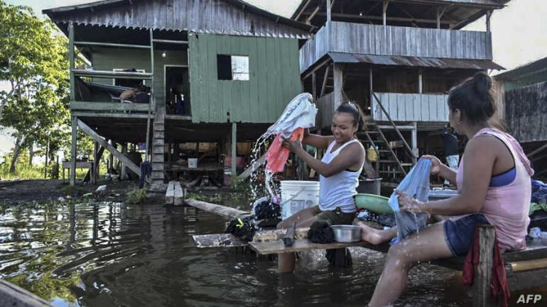 Women wash clothes at the Amazon river in Leticia, Colombia on May 13, 2020, amid the new coronavirus pandemic. - Colombia will increase the presence of military personnel on the Amazon border that shares with Brazil and Peru due to the COVID-19 outbreak hitting that helpless and poor region, and that has already reached the departmental prison. (Photo by Tatiana Alvarez / AFP)