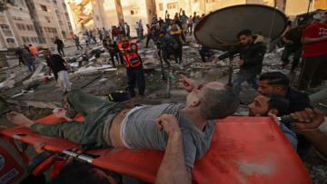 Palestinians carry one of survivers from under the rubble of a building, after it was struck by Israeli strikes, in Gaza City, May 16, 2021. - Israeli forces pummeled the densely populated Gaza Strip, the sixth day of bombardments on the Palestinian enclave controlled by Islamist group Hamas, which fired back rocket barrages. (Photo by MOHAMMED ABED / AFP)