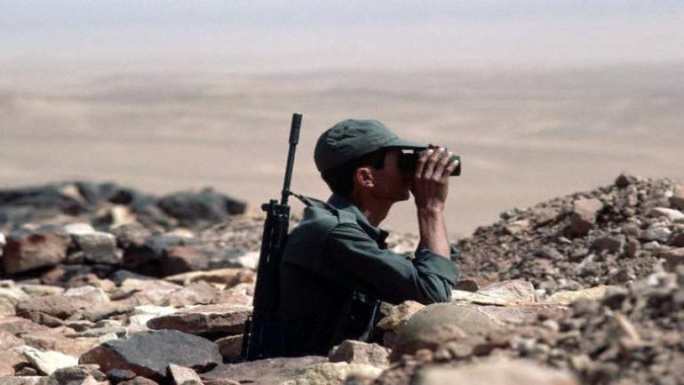 ca. October 1985, Western Sahara --- A Moroccan soldier looks through binoculars at the defense wall in Guelta-Zimmour, on the lookout for members of the Polisario. Morocco annexed and occupied parts of Western Sahara, and there is armed conflict between Moroccan occupying forces and the Polisario, a guerilla group fighting in support of the indigenous people of Western Sahara. --- Image by © Peter Turnley/CORBIS