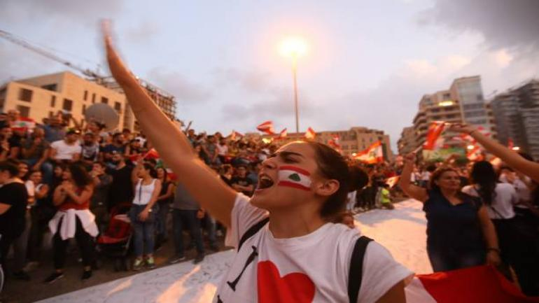 TOPSHOT - Lebanese demonstrators chant slogans as they take part in a rally in the capital Beirut's downtown district on October 20, 2019. - Thousands continued to rally despite calls for calm from politicians and dozens of arrests. The demonstrators are demanding a sweeping overhaul of Lebanon's political system, citing grievances ranging from austerity measures to poor infrastructure. (Photo by Anwar AMRO / AFP) (Photo by ANWAR AMRO/AFP via Getty Images)
