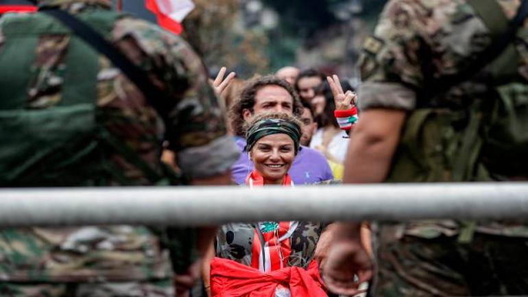TOPSHOT - A protester draped in the Lebanese national flag flashes the victory gesture as she stands before Lebanese army soldiers during a demonstration on the seventh day of protest against tax increases and official corruption, in Zouk Mosbeh, north of the capital Beirut, on October 23, 2019. - The almost one-week-old massive street protests in Lebanon, sparked by a tax on messaging services such as WhatsApp, have morphed into a united condemnation of a political system seen as corrupt and beyond repair. (Photo by JOSEPH EID / AFP) (Photo by JOSEPH EID/AFP via Getty Images)