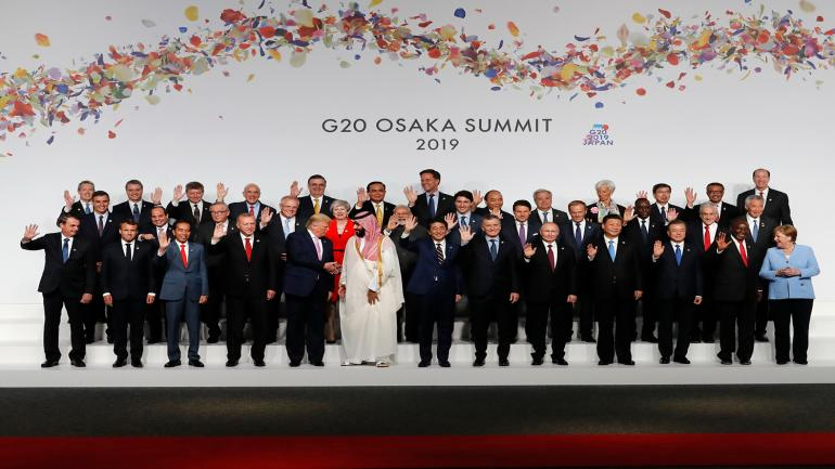 US President Donal Trump (C-L) chats with Saudi Arabia's Crown Prince Mohammed bin Salman (C-R) as other leaders wave during a family photo at the G20 Summit in Osaka on June 28, 2019. (Photo by KIM KYUNG-HOON / POOL / AFP)