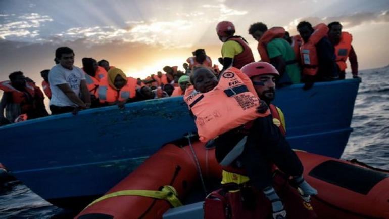 A child from African origin is rescued from a distressed vessel by a member of Proactiva Open Arms NGO in the mediteranean sea some 20 nautical miles north of Libya on October 3, 2016. Italy coordinated the rescue of more than 5,600 migrants off Libya, three years to the day after 366 people died in a sinking that first alerted the world to the Mediterranean migrant crisis. / AFP PHOTO / ARIS MESSINIS