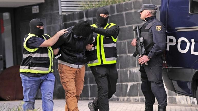 Members of the Spanish National Police escort an arrested man accused of collaborating with the Islamic State in San Sebastian on October 11, 2016. Spanish police have arrested two men on suspicion of seeking recruits for the Islamic State group, the interior ministry said today. / AFP PHOTO / ANDER GILLENEA