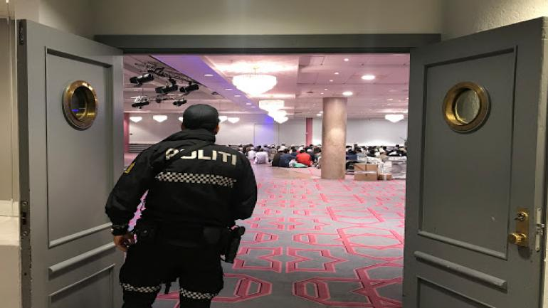 A Norwegian police officer looks on as people gather before morning prayer in Thon Oslofjord hotel in Sandvika, Norway August 11, 2019. REUTERS/Lefteris Karagiannopoulos